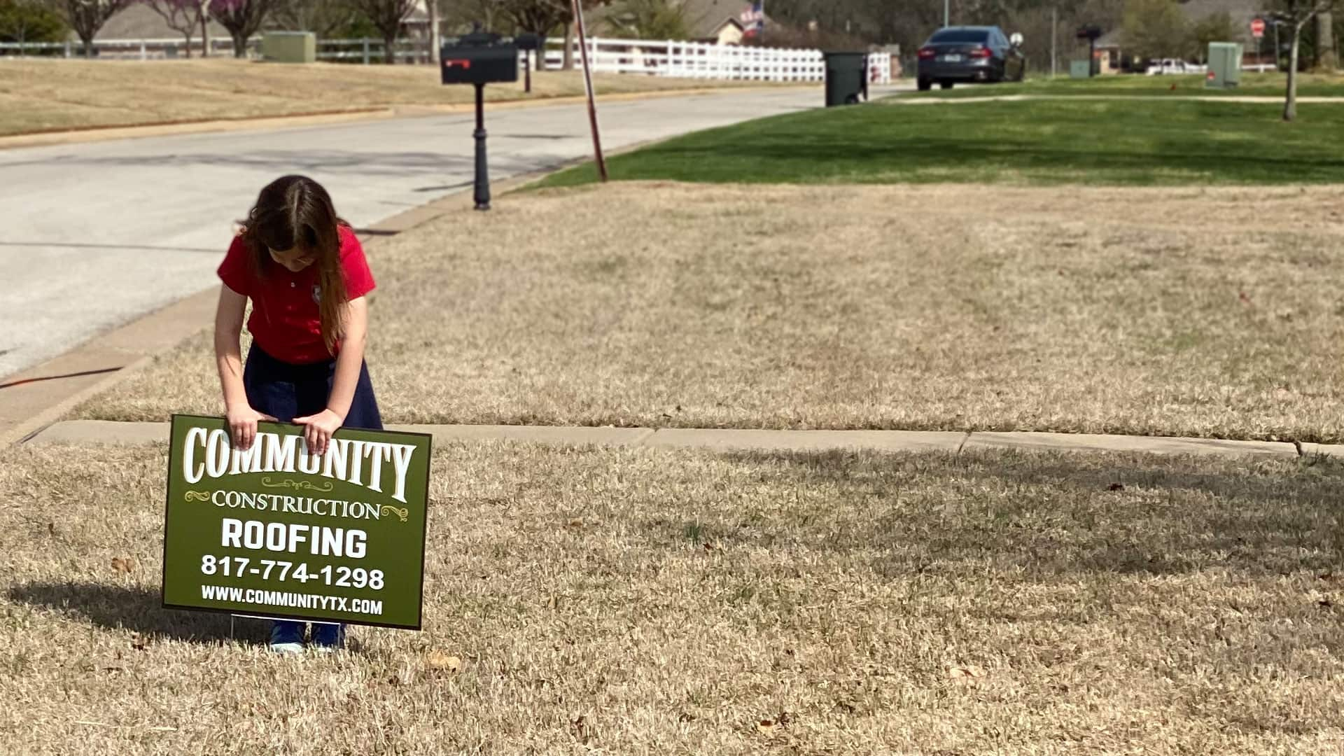 Girl placing sign in lawn